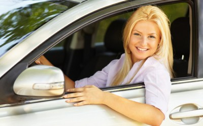 Excited teenage female driver sitting in a vehicle