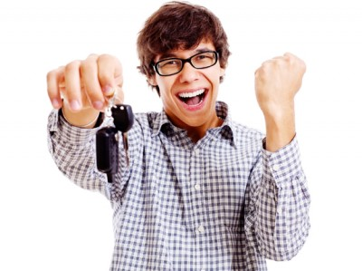Excited teenage male driver holding a key