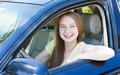 Excited teenate female driver sitting in vehicle