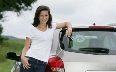 Excited teenage female driver standing next to car