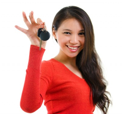 Excited teen female driver holding vehicle key